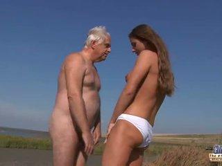Unge barmfager goddess riding gammel mann i en vill faen på den strand