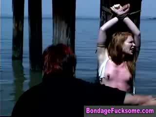 Palaistuve tied apkārt a pole ārā uz the ocean gets visi whipped