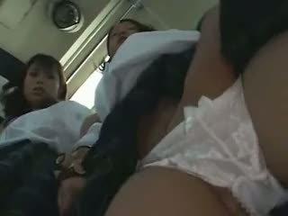 Two schoolgirls betast in een bus