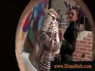 Two glam sluts making uit en spelen met lul bij de gloryhole