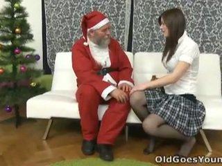 Vecchio santa clause gives giovane giovanissima un gift
