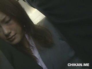 Businessgirl หมู่ โดย stranger ใน a crowded รถไฟ