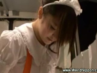 Asiatiskapojke servitris uses en leksak medan serving