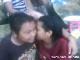 Aziatisch lesbisch koppel smooching infront van friends